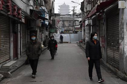 Personas con máscaras en un callejón cerca de la Torre de la Grulla Amarilla en Wuhan, el epicentro del nuevo brote de coronavirus, provincia de Hubei, el 27 de febrero de 2020 (REUTERS/Stringer)
