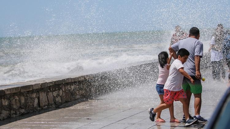 Un padre escapa junto a sus dos hijos de una ola que rompe muy cerca