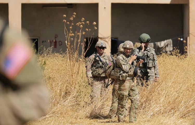 Soldados turcos y estadounidenses parados ante un punto militar de las Unidades de Protección del Pueblo kurdas cerca de Tel Abyad, Siria, en una foto de septiembre de 2019 (REUTERS/Rodi Said/archivo)