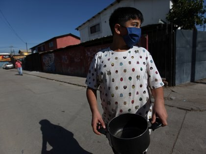 A child holds up a pot as he prepares to receive food rations at a so called 'Olla comun', a communal cook-up to provide plates of hot food to those with dwindling incomes or nothing at all at Puente Alto area, as the spread of the coronavirus disease (COVID-19) continues in Santiago, Chile May 14, 2020. Picture taken May 14, 2020. REUTERS/Ivan Alvarado