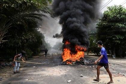 """FOTO DE ARCHIVO: Un manifestante antigolpista pasa junto a neumáticos en llamas después de que activistas lanzaran un """"ataque de basura"""" contra el régimen militar, en Yangon, Myanmar, el 30 de marzo de 2021. REUTERS / Stringer"""