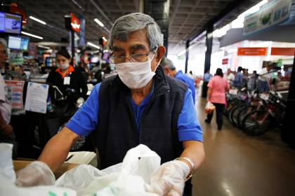An elderly man, working as a packer at a supermarket, wears a protective face mask as a security measure for the coronavirus disease (COVID-19), in Mexico City, Mexico March 17, 2020. Picture taken March 17, 2020. REUTERS/Gustavo Graf