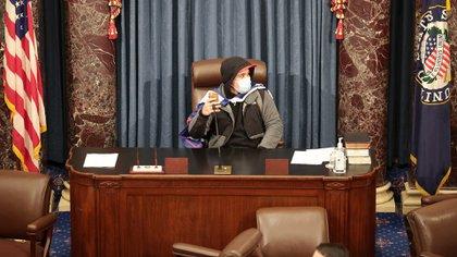 Un partidario de Trump se sienta en la silla de la presidencia del Senado luego de irrumpir en el Capitolio. Foto: Win McNamee/Getty Images/AFP