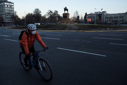 Un ciclista con mascarilla como medida para evitar el contagio con coronavirus para frente a la Plaza Italia el 16 de mayo de 2020 en Santiago (Chile). EFE/Alberto Valdés.