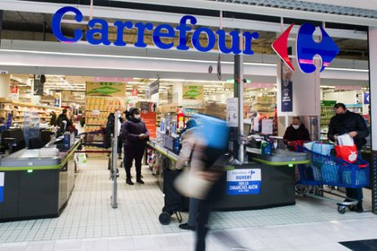 Shoppers at check-out counters of a Carrefour SA supermarket in Paris, France, on Wednesday, Jan. 13, 2021. Alimentation Couche-Tard Inc., the Canadian convenience-store operator that owns the Circle K chain, is exploring a takeover of French grocer Carrefour SA, a deal that would create a trans-Atlantic retail giant.