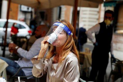 Una mujer con una máscara toma un café en un bar de Roma tras el levantamiento de las restricciones en mayo (Reuters/ Yara Nardi)