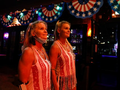 Waitresses watch firework displays in the sky as they celebrate the U.S. 4th of July Independence Day holiday, in Fort Lauderdale, Florida, U.S., July 4, 2020. REUTERS/Marco Bello