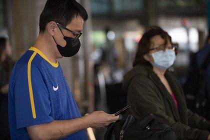 Pasajeros con mascarillas arriban al Aeropuerto Internacional de San Pablo (AP)