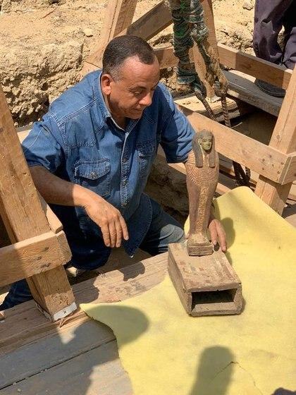 Mostafa al-Waziri, secretario general del Consejo Supremo de Antigüedades de Egipto, observa una estatua encontrada en uno de los ataúdes de 2500 años descubiertos en un pozo funerario en el desierto cerca de la necrópolis de Saqqara (Reuters)
