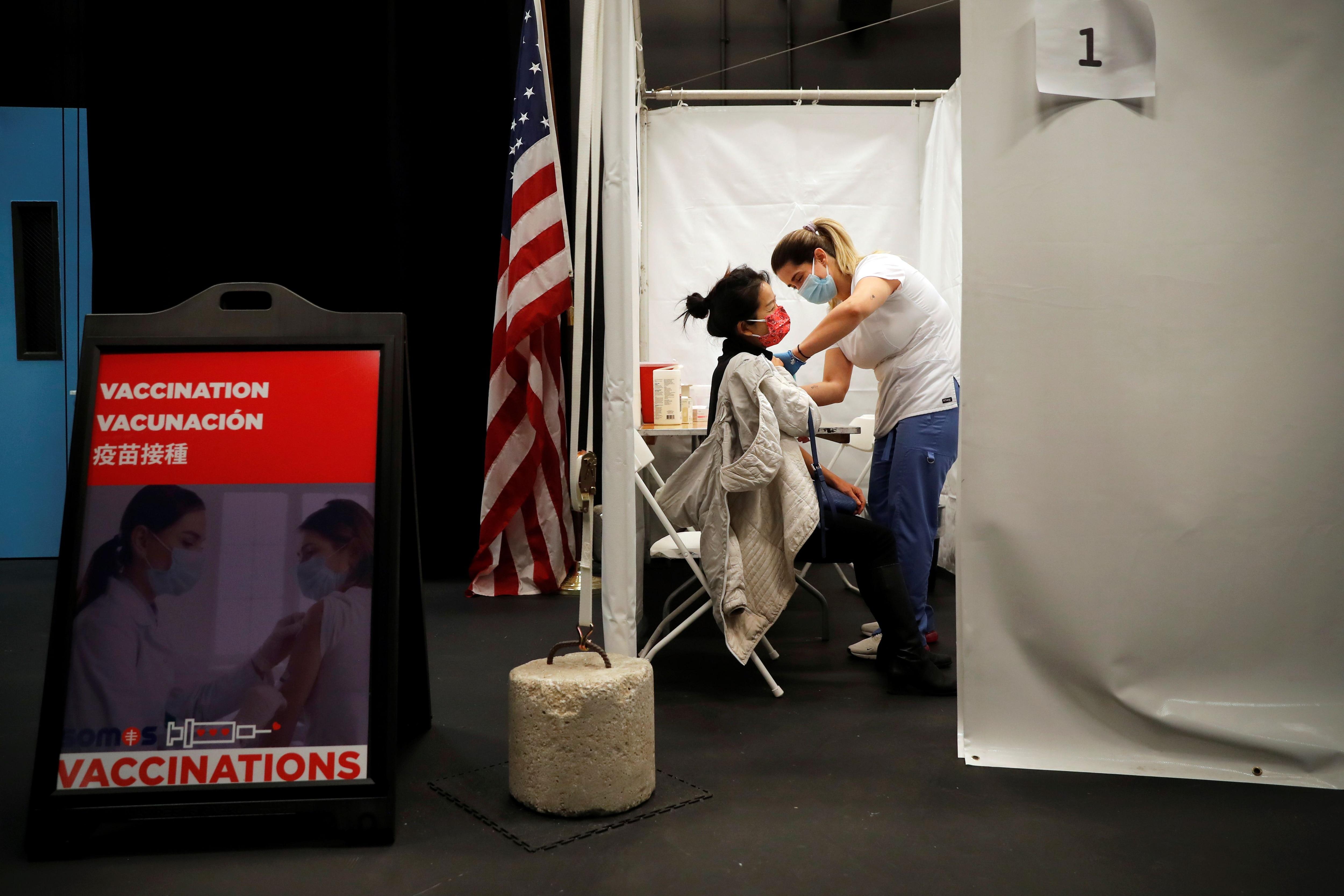 Un trabajador sanitario administra una inyección de la vacuna Moderna COVID-19 a una mujer en un centro de vacunación emergente operado por SOMOS Community Care durante la pandemia de la enfermedad del coronavirus (COVID-19) en Manhattan en la ciudad de Nueva York, Nueva York, Estados Unidos, 29 de enero de 2021. REUTERS