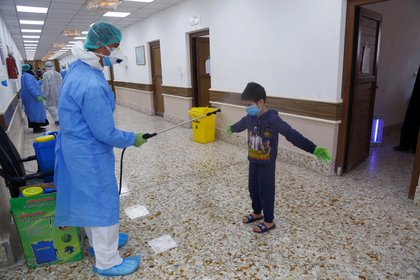 A nurse wearing protective suit and face mask sprays a boy who was infected with the coronavirus disease (COVID-19) and has recovered, with sterile water, in a quarantine ward, at a hospital in the holy city of Najaf, Iraq April 21, 2020. REUTERS/Alaa al-Marjani