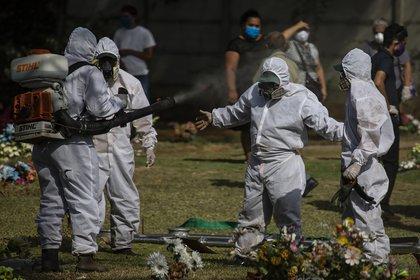 Los sepultureros se desinfectan después de enterrar un cuerpo en Managua, Nicaragua