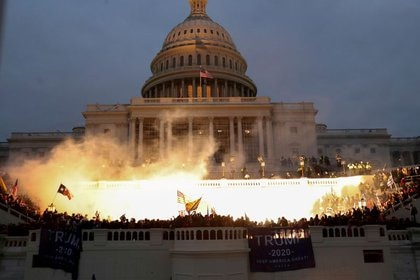 Se ve una explosión causada por una munición policial mientras los partidarios del presidente de los Estados Unidos, Donald Trump, se reúnen frente al edificio del Capitolio de los Estados Unidos en Washington, Estados Unidos
