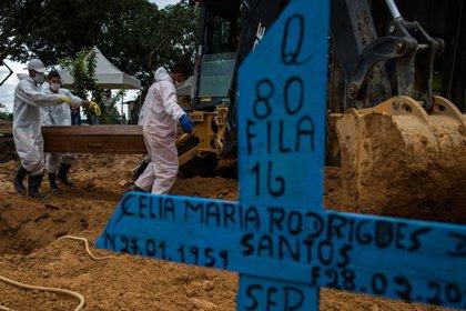 Varias personas asisten al funeral de una víctima del COVID-19 en el Cementerio de Nossa Senhora Aparecida, en Manaos, el 1 de marzo de 2021. EFE/Raphael Alves