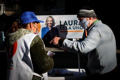 Dos ciudadanos fueron registrados al hablar frente a un afiche de la candidata a la Intendencia de Montevideo Laura Raffo, en Montevideo (Uruguay). EFE/Raúl Martínez