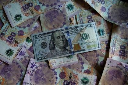 FOTO DE ARCHIVO. Un billete de cien dólares estadounidenses sobre billetes de cien pesos de Argentina. 3 de septiembre de 2019. REUTERS/Agustín Marcarián