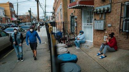 Las primas Idenia Ferrera, a la izquierda, y Kimberly Ferrera, a la derecha, se sientan fuera de su casa en Corona, Queens, y siguen las instrucciones de no salir durante la pandemia. (Ryan Christopher Jones / The New York Times)