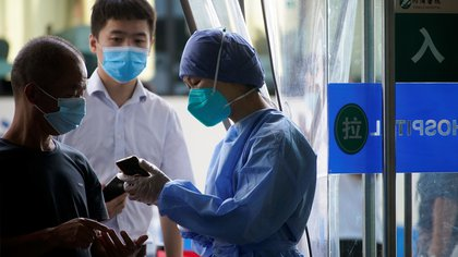 A worker wearing a face mask holds a mobile phone during a government organised media tour at Tongji Hospital following the coronavirus disease (COVID-19) outbreak, in Wuhan, Hubei province, China September 3, 2020. REUTERS/Aly Song
