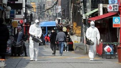 Trabajadores de cuarentena rocían desinfectantes en la zona de bares nocturnos del barrio de Itaewon, tras el brote de coronavirus en Seúl, Corea del Sur (Reuters)