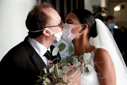 Los recién casados Diego Fernandes, de 46 años, y Deni Salgado, de 30, se besan con máscaras protectoras en una ceremonia de boda con solo testigos y sin invitados, ya que las reuniones públicas están prohibidas como parte de las medidas de bloqueo de Italia para prevenir la propagación de la enfermedad por coronavirus (COVID-19) en Nápoles, Italia. 20 de marzo de 2020. REUTERS/Ciro De Luca