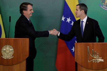El líder de la oposición venezolana Juan Guaidó le da la mano al presidente de Brasil Jair Bolsonaro después de una reunión en Brasilia, Brasil el 28 de febrero de 2019.