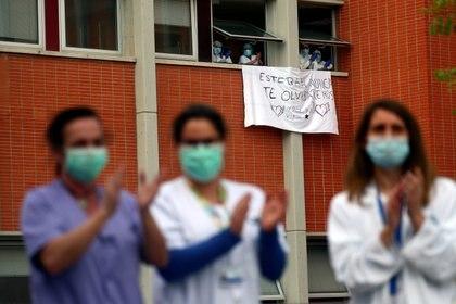 Trabajadores aplauden junto a una bandera por Esteban, un enfermero que murió por coronavirus (Reuters)