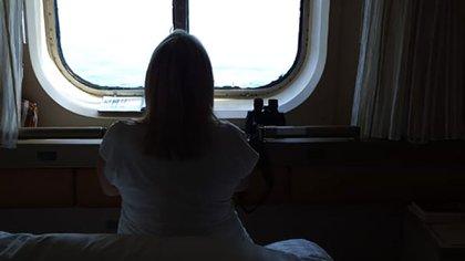Claudia mirando por la ventana del anterior camarote, en el barco donde fallecieron 4 pasajeros
