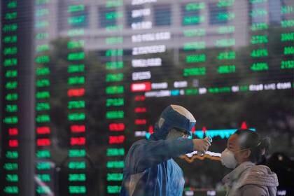 Un trabajador en traje de protección mide la temperatura corporal de una mujer en el edificio de la Bolsa de Valores de Shanghai, en China. 28 de febrero de 2020 (REUTERS/Aly Song)