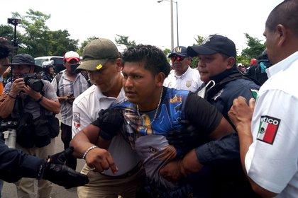 AME549. TAPACHULA (MÉXICO), 05/06/2019.-Miembros del Instituto Nacional de Migración (INAMI), y policías federales detienen a migrantes centroamericanos este miércoles, en Tapachula, en el estado de Chiapas (México). Autoridades federales y migratorias mexicanas frenaron este miércoles una caravana de uno 500 migrantes que se internó en la frontera sur de México y que tenía como destino Estados Unidos. La caravana cruzó por la mañana de este miércoles el puente fronterizo entre Guatemala y México sin que las autoridades migratorias mexicanas lograran detenerlos, según informan medios locales. EFE/ Calos López