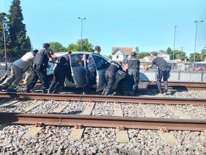 El vehículo fue rescatado por policías y transeúntes que lo empujaron para removerlo de las vías del tren.