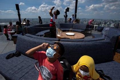 Personas en Bangkok, Thailand, observan el eclipse de 2019 -. REUTERS/Athit Perawongmetha