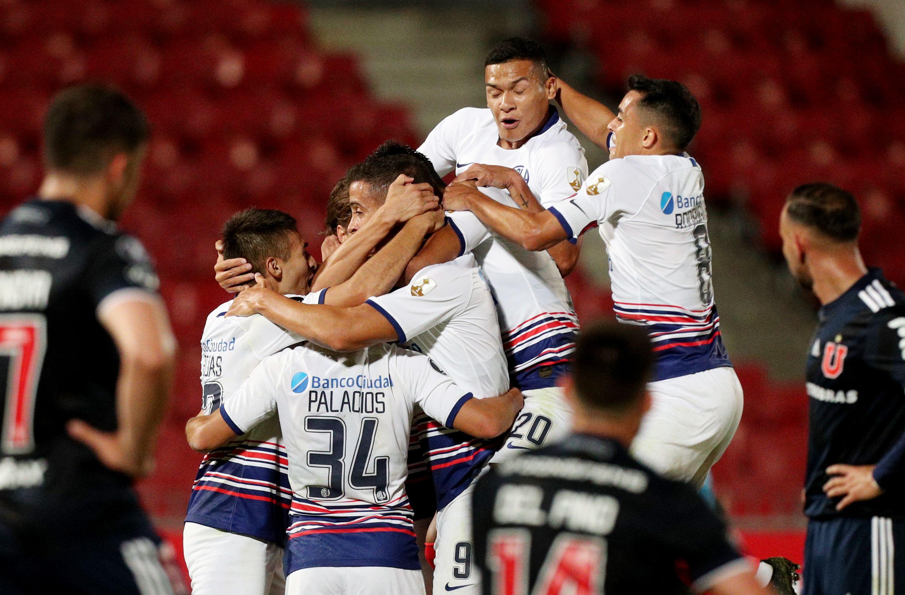 Todo San Lorenzo abraza a Franco Di Santo, el autor del gol del empate en Chile ante la U. (REUTERS/Esteban Felix)
