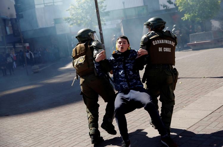 Dos agentes se llevan a un joven (REUTERS/Juan Gonzalez)