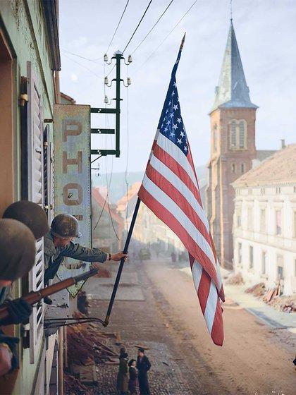 El capitán Thomas H. Garrahan, del Regimiento de Infantería 398, iza una bandera de los Estados Unidos en la ciudad francesa de Bitche. La bandera fue confeccionada en secreto por una niña