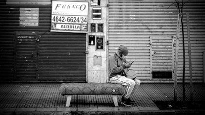 Un hombre revisa su celular frente a locales comerciales cerrados en Buenos Aires, reflejo de la profunda crisis que generó la cuarentena extendida (EFE)