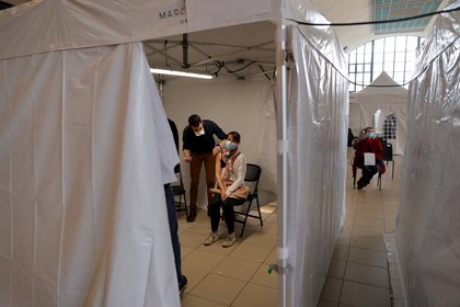 Una mujer, con una mascarilla protectora, recibe una dosis de la vacuna Moderna COVID-19 en un centro de vacunación en Marcq-en-Baroeul como parte de la campaña de vacunación contra la enfermedad por coronavirus en Francia (Reuters)