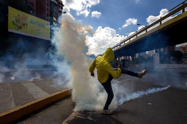 Un manifestante patea una bomba de gas lacrimógeno lanzada por la policía militar chavista(EFE)