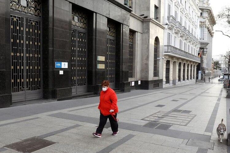 Una mujer, con una máscara protectora, camina con su perro por la vacía calle de Alcalá durante el confinamineto parcial, como parte de un estado de alarma de 15 días para combatir el brote de coronavirus en Madrid, España, el 15 de marzo, 2020. REUTERS/Sergio Perez