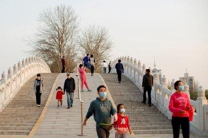 Foto del lunes de un grupo de personas usando máscaras protectoras contra el coronavirus paseando por Pekín.  Mar 23, 2020. REUTERS/Thomas Peter