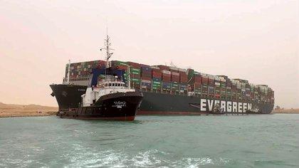 Un barco navega frente al enorme carguero MV Ever Green, luego de que giró de lado en el Canal de Suez de Egipto, bloqueando el tráfico en un vía navegable Este-Oeste crucial para el transporte marítimo mundial (Autoridad del Canal de Suez vía AP)