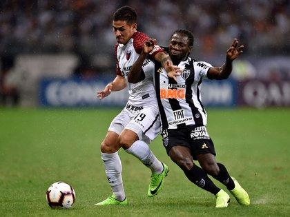 Alex Vigo disputa la pelota ante el colombiano Yimmi Chara del Atlético Mineiro (Photo by Douglas Magno / AFP)