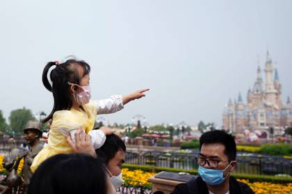 Una niña junto a sus padres en Shanghai Disney Resort. REUTERS/Aly Song