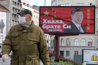 """FOTO DE ARCHIVO: Un hombre con una máscara protectora pasa por un cartel que muestra al presidente chino Xi Jinping en Belgrado, Serbia, el 1 de abril de 2020. El texto de la valla publicitaria dice """"Gracias, hermano Xi"""". REUTERS/Djordje Kojadinovic"""