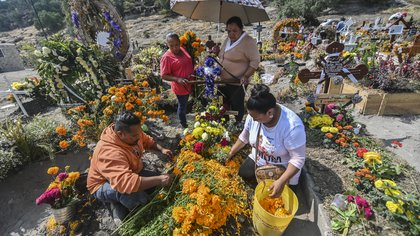 People decorate a relative's grave prior to the Day of the Dead at the Municipal Pantheon in Valle de Chalco, Mexico state, Mexico, on October 28, 2020, amid the COVID-19 coronavirus pandemic. (Photo by PEDRO PARDO / AFP)