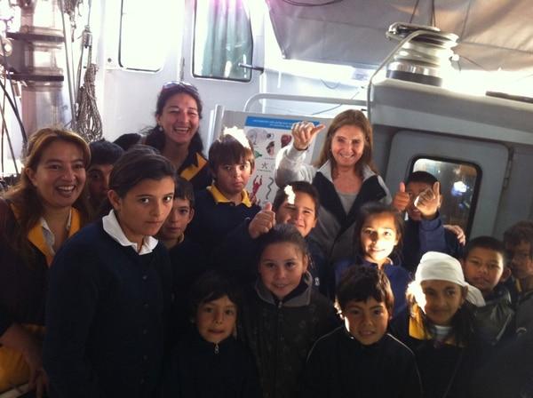 Cora de Alvear (mano levantada) rodeada de alumnos que visitaron la exposición flotante en su recorrido por el Paraná (2016)