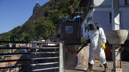 25/07/2020 25 July 2020, Brazil, Rio de Janeiro: A resident of the slum Santa Marta disinfects the favela in the Botafogo district during the coronavirus pandemic. Photo: Fernando Souza/dpa