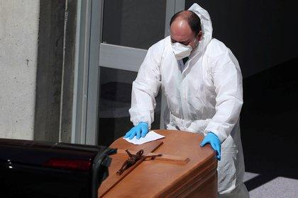 Un empleado de una funeraria traslada el ataúd de una víctima del coronavirus, en Leganés, España, uno de los países europeos más afectados por la pandemia.
