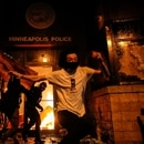 Protesters react as they set fire to the entrance of a police station as demonstrations continue after a white police officer was caught on a bystander's video pressing his knee into the neck of African-American man George Floyd, who later died at a hospital, in Minneapolis, Minnesota, U.S., May 28, 2020. REUTERS/Carlos Barria