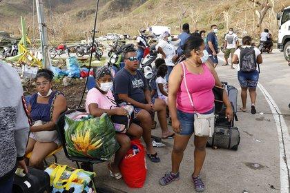Isle�os esperan en fila para ingresar a alguno de los vuelos humanitarios de la Fuerza �rea que parten desde el aeropuerto El Embrujo hac�a la isla de San Andr�s, el 21 de noviembre de 2020, en Providencia (Colombia). EFE/Mauricio Due�as Casta�eda