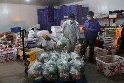 Trabajadores con máscaras faciales empacan vegetales en el mercado de Baishazhou en Wuhan, el 19 de febrero de 2020. (Diario de China vía REUTERS)